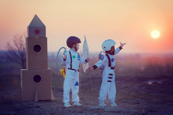 Two kids in Astronaut costumes standing next to cardboard rocket ship holding flag and pointing toward the setting sun